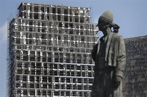 A statue is seen in front of a building that was damaged