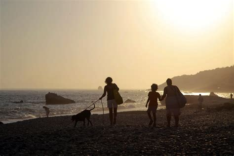 People walk by the sea at Aphrodite's Rock near Paphos